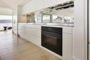 The cooking zone features a stainless benchtop and Wolf appliances