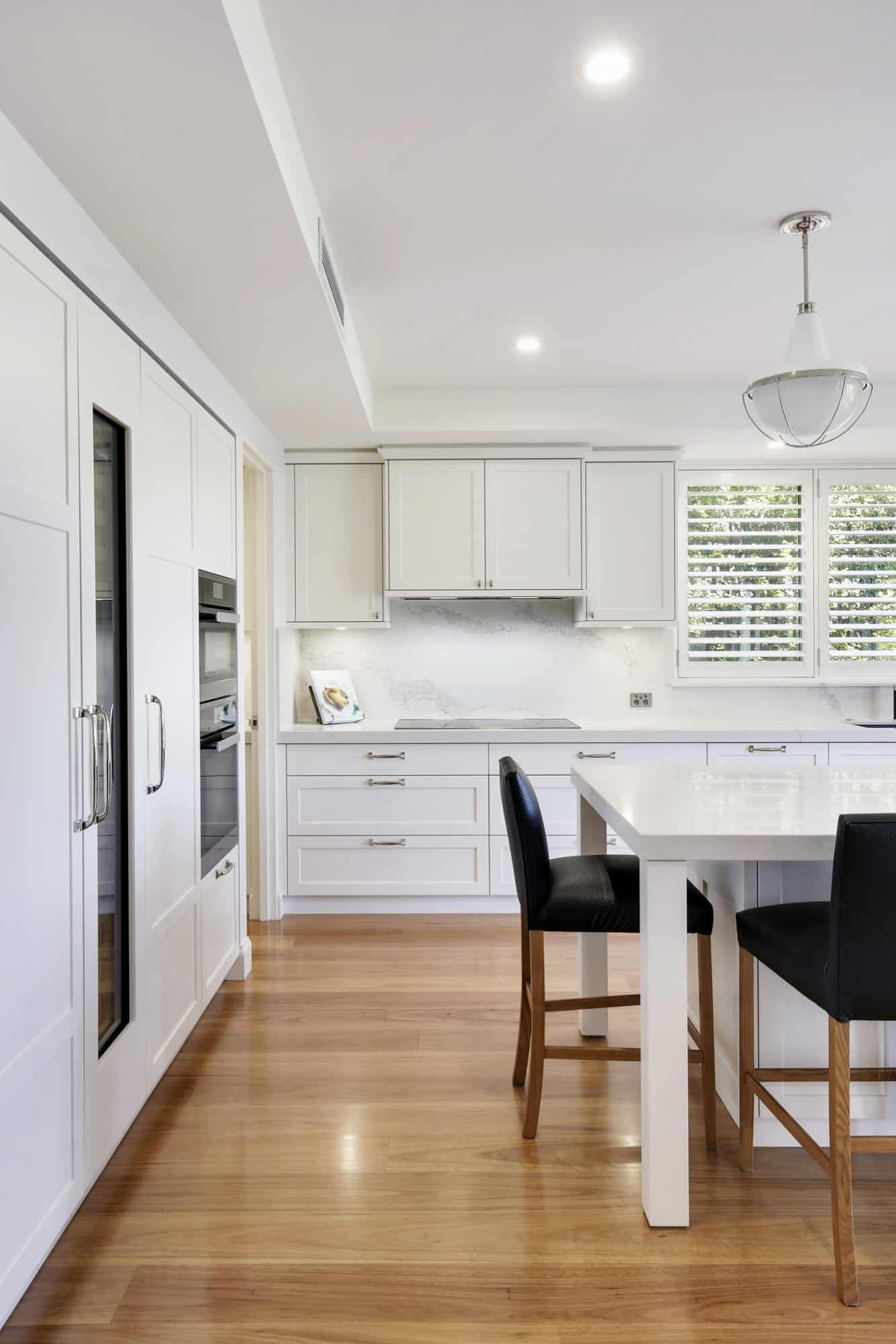 White shaker kitchen with wide timber planked flooring