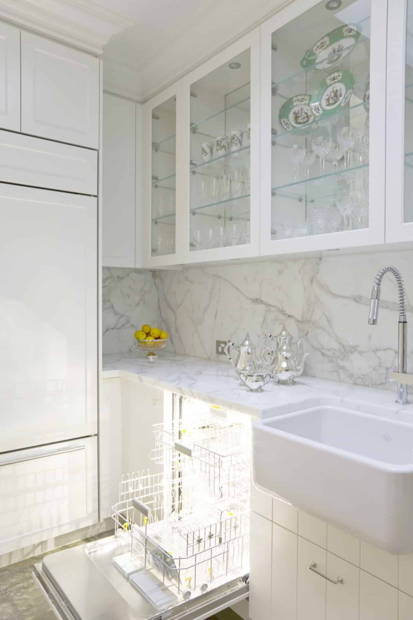 Luxurious scullery with integrated dishwasher behind a v groove door