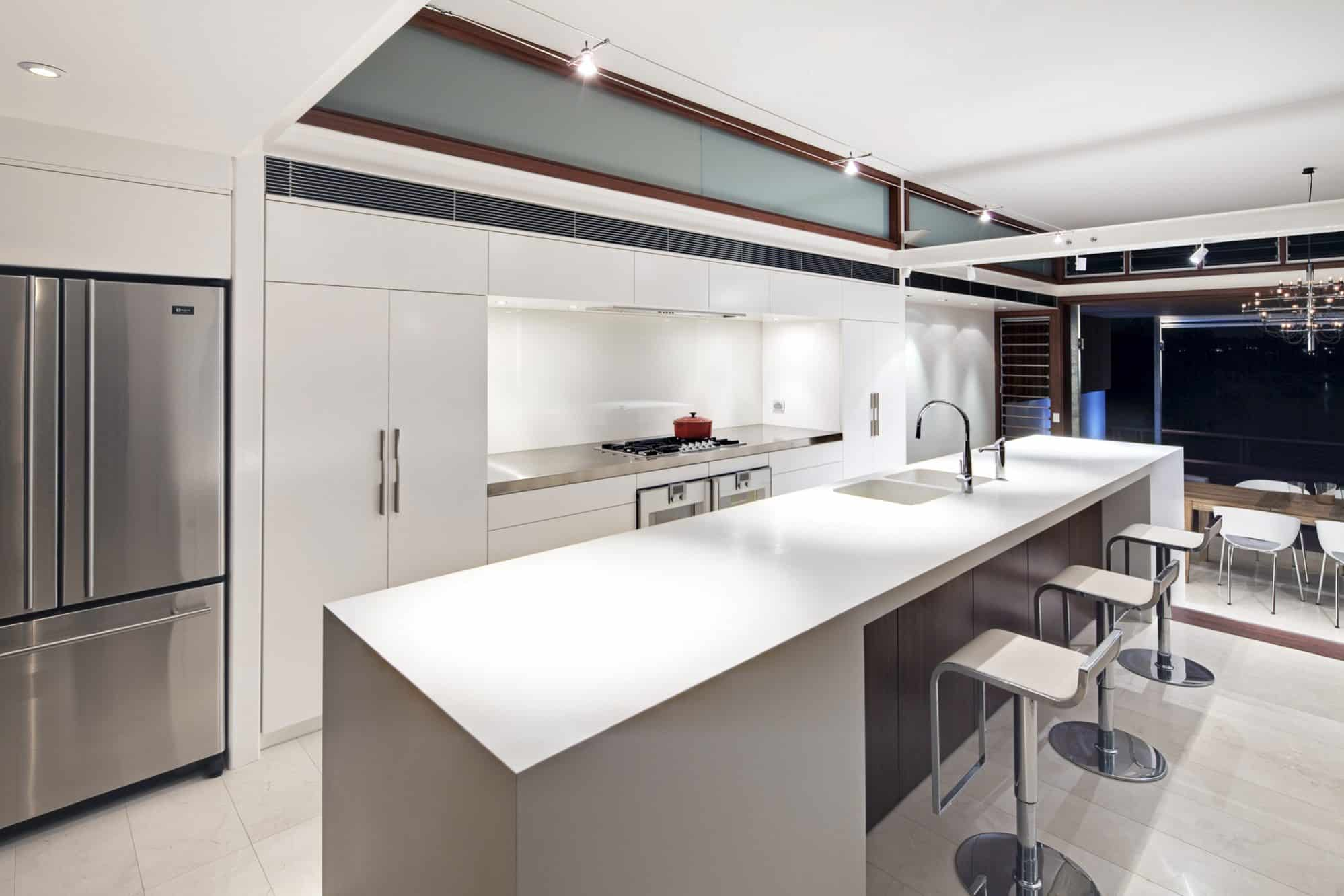 White kitchen with a long seamless island in Corian
