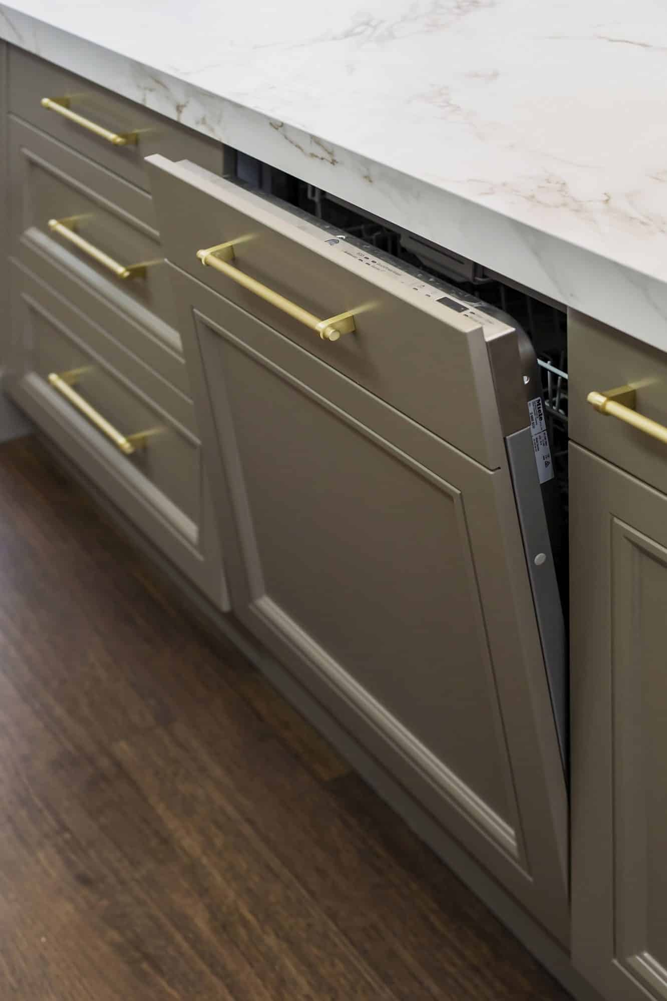 Integrated Miele dishwasher hidden behind a detailed kitchen door
